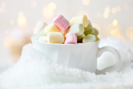 Merry Christmas and happy New year. Cup of cocoa and marshmallows on a light background. Background with copy space. Selective focus. Christmas background.