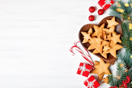Merry Christmas and happy New year. Cookies, gifts and fir-tree branches on a white wooden table. Selective focus. Christmas background. Horizontal. Background with copy space. Stock Photo