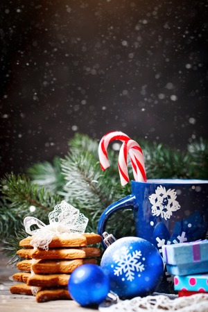 Merry Christmas and happy New year. Cup cocoa, cookies, gifts and fir-tree branches on a wooden table. Selective focus. Christmas background. Background with copy space.