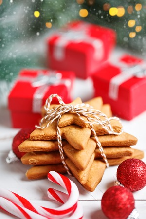 Merry Christmas and happy New year. Cookies, gifts and fir-tree branches on a white wooden table. Selective focus. Christmas background.