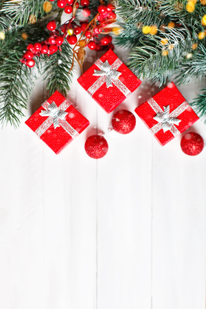 Merry Christmas and happy New year. Gifts and fir-tree branches on a white wooden table. Selective focus. Christmas background. Vertical. Top view.