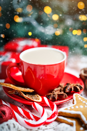 Merry Christmas and happy New year. Cup of cocoa, cookies, gifts and fir-tree branches on a white wooden table. Selective focus. Christmas background. Horizontal.