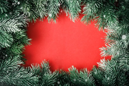 Merry Christmas and happy New year. A frame of fir-tree branches on a red background. Selective focus. Christmas background. Horizontal. Background with copy space.