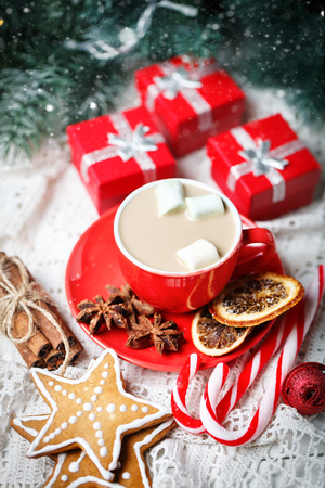 Merry Christmas and happy New year. Cup of cocoa, gifts and fir-tree branches on a white wooden table. Selective focus. Christmas background. Vertical.