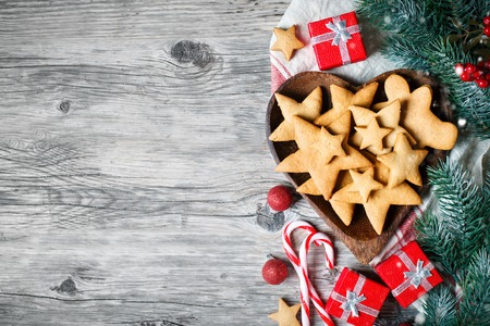 Merry Christmas and happy New year. Cookies, gifts and fir-tree branches on a wooden table. Selective focus. Christmas background. Background with copy space.