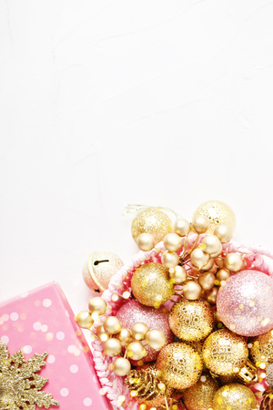 Merry Christmas and happy New year. Golden Christmas toys on a light background. Selective focus. Top view.