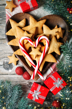 Merry Christmas and happy New year. Cookies, gifts and fir-tree branches on a wooden table. Christmas background. Stock Photo