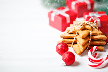 Merry Christmas and happy New year. Cookies, gifts and fir-tree branches on a white wooden table. Christmas background.