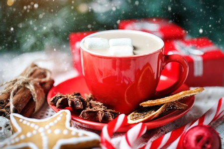 Merry Christmas and happy New year. Cup of cocoa, cookies, gifts and fir-tree branches on a white wooden table.