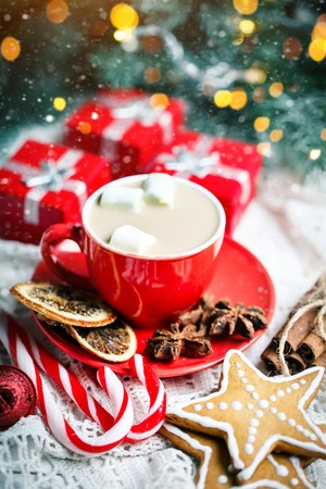 Merry Christmas and happy New year. Cup of cocoa, cookies, gifts and fir-tree branches on a white wooden table. Selective focus. Christmas background. Vertical.