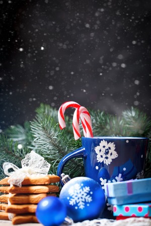 Merry Christmas and happy New year. Cup cocoa, cookies, gifts and fir-tree branches on a wooden table. Selective focus. Christmas background. Background with copy space. Vertical.