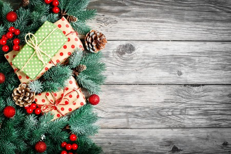 Merry Christmas and happy New year. Spruce branches and Christmas toys on a wooden background. Background with copy space. Selective focus. Top view. Christmas background. Horizontal.