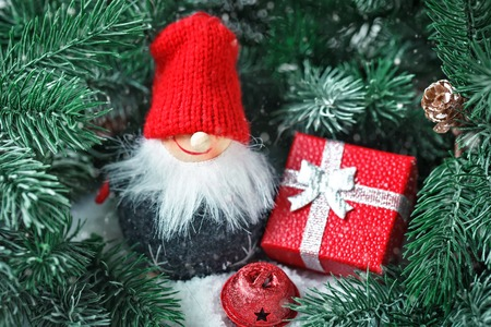 Merry Christmas and happy New year. Toy Santa in the branches of a spruce. Horizontal. Selective focus.