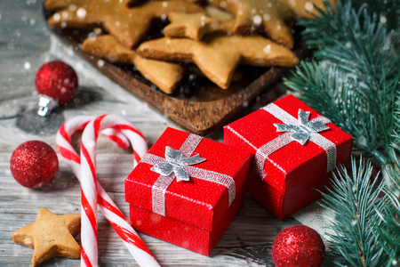 Merry Christmas and happy New year. Cookies, gifts and fir-tree branches on a wooden table. Selective focus. Christmas background. Horizontal.