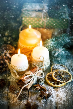 Merry Christmas and happy New year. Candle and Christmas toys on a wooden table. Bokeh. Selective focus. Stock Photo