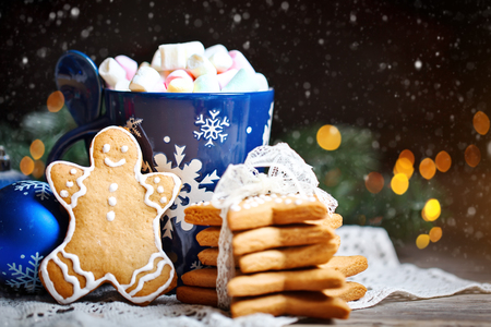 Merry Christmas and happy New year. Cup cocoa, cookies, gifts and fir-tree branches on a wooden table. Selective focus. Christmas background. Stock Photo