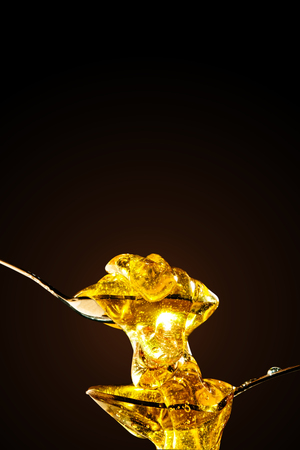 Honey with gold color flows down from a spoon, on a dark background. Healthy eating. Diet. Selective focus. Background with copy space.