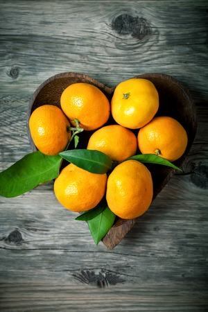 Tangerines with leaves in basket on rustic wooden background.