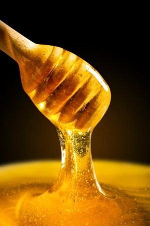 Honey with gold color flows down from a spoon. Healthy food concept. Healthy eating. Diet. Selective focus. Macro.