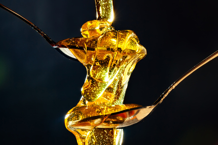 Honey with gold color flows down from a spoon, on a dark background. Healthy eating. Diet. Selective focus.