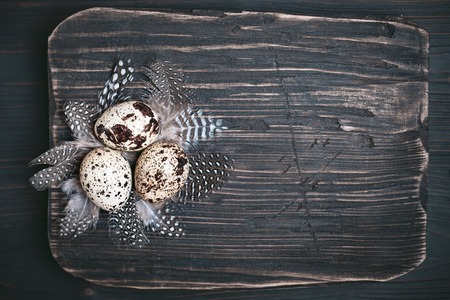 Quail eggs on old wooden background. Happy Easter. Top view. Free copy space. Selective focus. Horizontal.