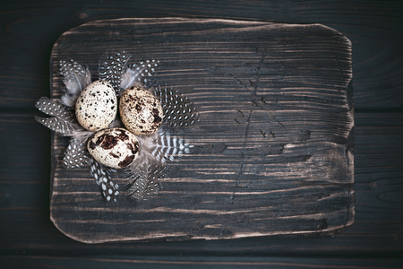 Quail eggs on old wooden background. Happy Easter. Top view. Free copy space. Selective focus.