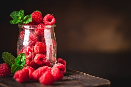 Raspberries in a Cup on a dark background. Summer and healthy food concept. Background with copy space. Selective focus. Vertical.