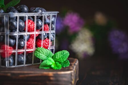 Raspberries and blueberry in a basket on a dark background. Summer and healthy food concept. Background with copy space. Selective focus.
