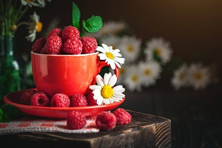 Raspberry in a red cup with chamomile and leaves on a dark background. Summer and healthy food concept. Background with copy space. Selective focus. Stockfoto - 128606798