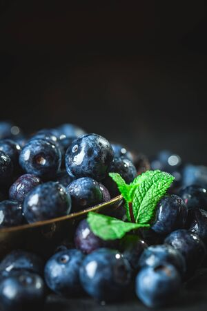 Juicy and fresh blueberries with green leaves on rustic table. Blueberry antioxidant. Concept for healthy eating and nutrition. Selective focus.