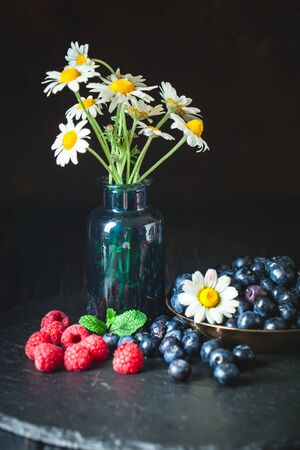 Raspberries and blueberries with chamomile and leaves on a dark background. Summer and healthy food concept. Background with copy space. Vertical. Stockfoto - 128606980