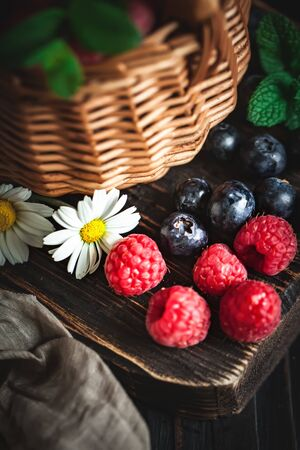 Raspberries and blueberries in a basket with chamomile and leaves on a dark background. Summer and healthy food concept. Selective focus. 版權商用圖片