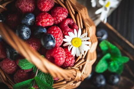 Raspberries and blueberries in a basket with chamomile and leaves on a dark background. Summer and healthy food concept. Selective focus. Stockfoto - 128606651