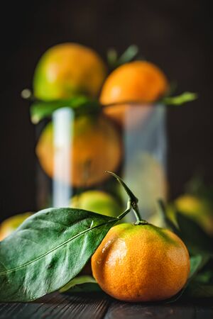 Tangerines with leaves on an old fashioned country table. Selective focus. Vertical.