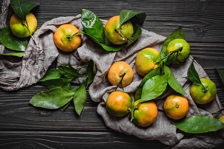 Tangerines with leaves on an old fashioned country table. Selective focus. Horizontal. Top view. 免版税图像