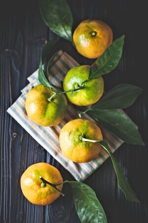 Tangerines with leaves on an old fashioned country table. Selective focus. Vertical. Background with copy space. Stock Photo