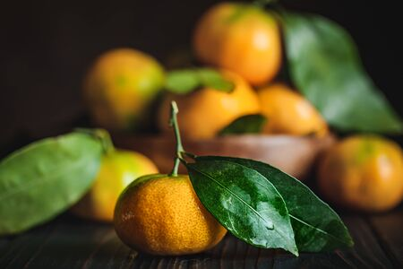 Tangerines with leaves on an old fashioned country table. Selective focus. Horizontal. Stock Photo