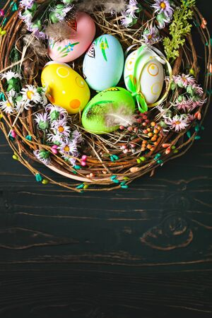 Happy Easter. Congratulatory easter background. Easter eggs and flowers. Background with copy space. Selective focus. Vertical.