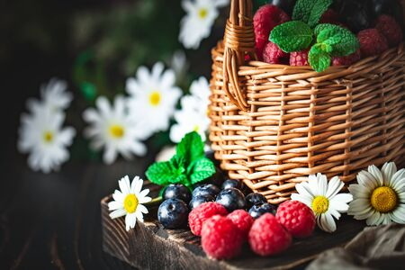 Raspberries and blueberries in a basket with chamomile and leaves on a dark background. Summer and healthy food concept. Selective focus.