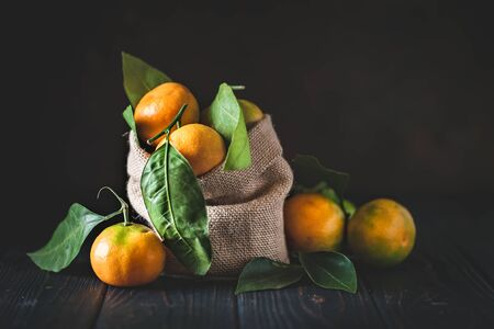 Tangerines with leaves on an old fashioned country table. Selective focus. Horizontal. Archivio Fotografico