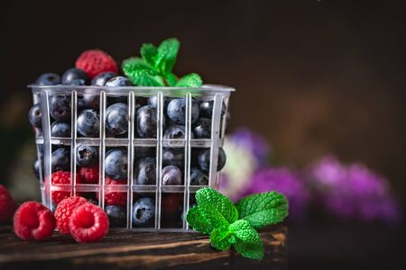 Raspberries and blueberry in a basket on a dark background. Summer and healthy food concept. Background with copy space. Selective focus. Archivio Fotografico - 149420913
