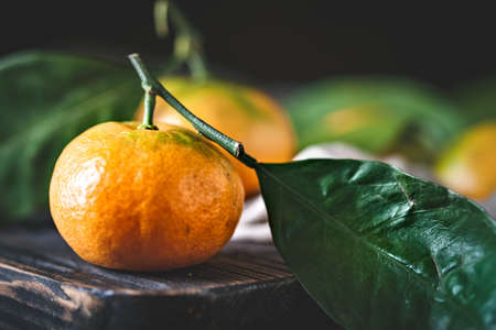 Tangerines with leaves on an old fashioned country table. Selective focus. Horizontal. Reklamní fotografie