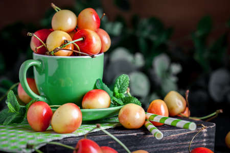 Fresh cherry in a Cup on a dark rustic wooden table. Background with space for copying. Selective focus. Archivio Fotografico - 151214996