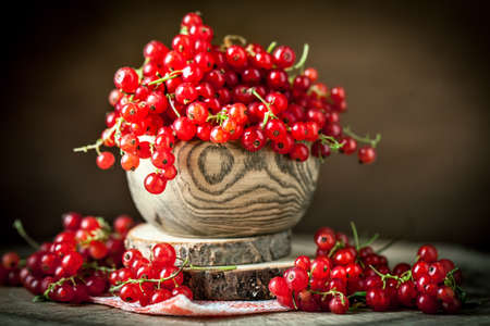 Fresh red currants in plate on dark rustic wooden table. Background with copy space. Selective focus. Banque d'images - 151050569