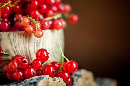 Fresh red currants in plate on dark rustic wooden table. Background with copy space. Selective focus. Banque d'images - 151051100