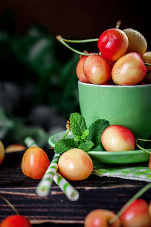 Fresh cherry in a Cup on a dark rustic wooden table. Background with space for copying. Selective focus. Archivio Fotografico - 151576099