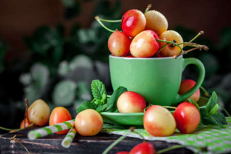 Fresh cherry in a Cup on a dark rustic wooden table. Background with space for copying. Selective focus. Banque d'images - 151872026