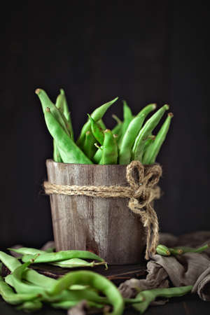 Fresh green beans on a wooden table. Summer and healthy food concept. Selective focus. Background with copy space.
