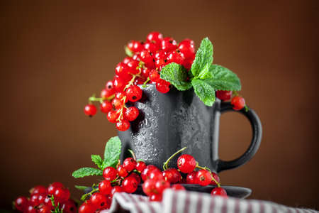 Fresh red currants in a Cup on a dark rustic wooden table. Background with space for copying. Selective focus. Imagens