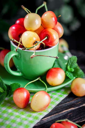 Fresh cherry in a Cup on a dark rustic wooden table. Background with space for copying. Selective focus.